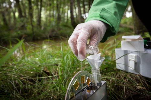 Activistas de Greenpeace toman muestras de agua que se analizarán en un laboratorio para determinar la presencia de sulfato.