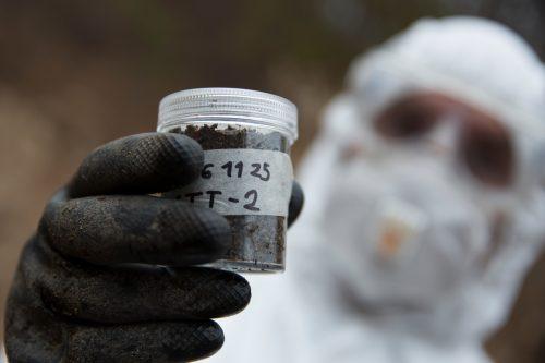 Un hombre con un traje de protección y guantes sujeta una muestra de tierra para analizar la radiación.