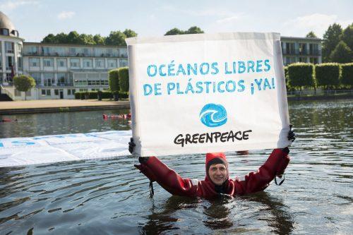Activista con pancarta Océanos libres de plásticos ya