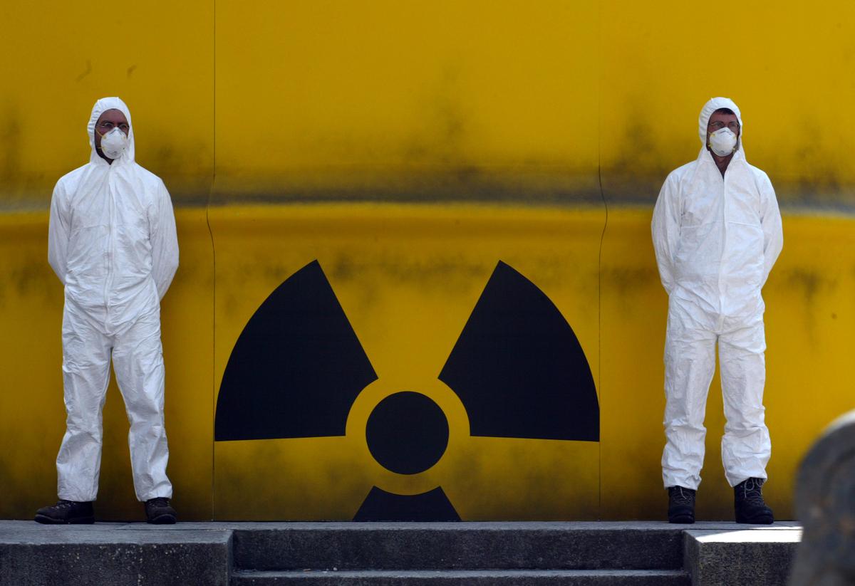 Dos activistas de Greenpeace con mascarillas y trajes de protección frente a un barril de residuos nucleares