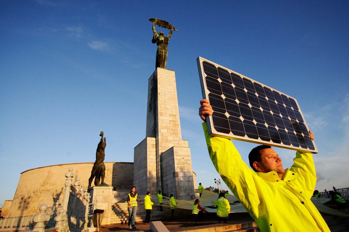 Un activista de Greenpeace sostiene un panel solar frente a la estatua de la Libertad de Budpest, Hungría