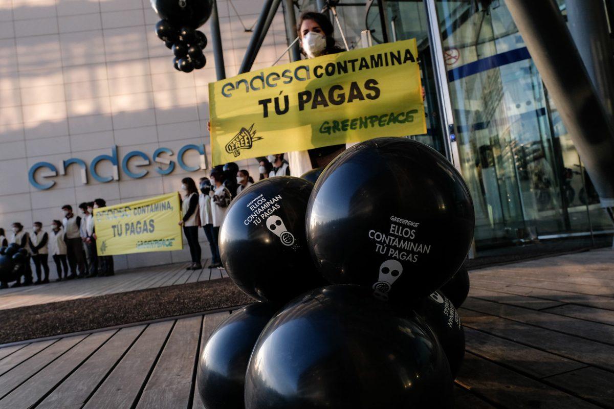 Activistas de Greenpeace sostienen globos en los que se puede leer 'Ellos contaminan tú pagas' frente a la sede de Endesa en Madrid