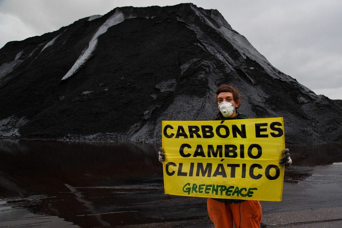 Una activista de Greenpeace delante de una montaña de carbón sujeta un cartel que dice Carbón es cambio climático