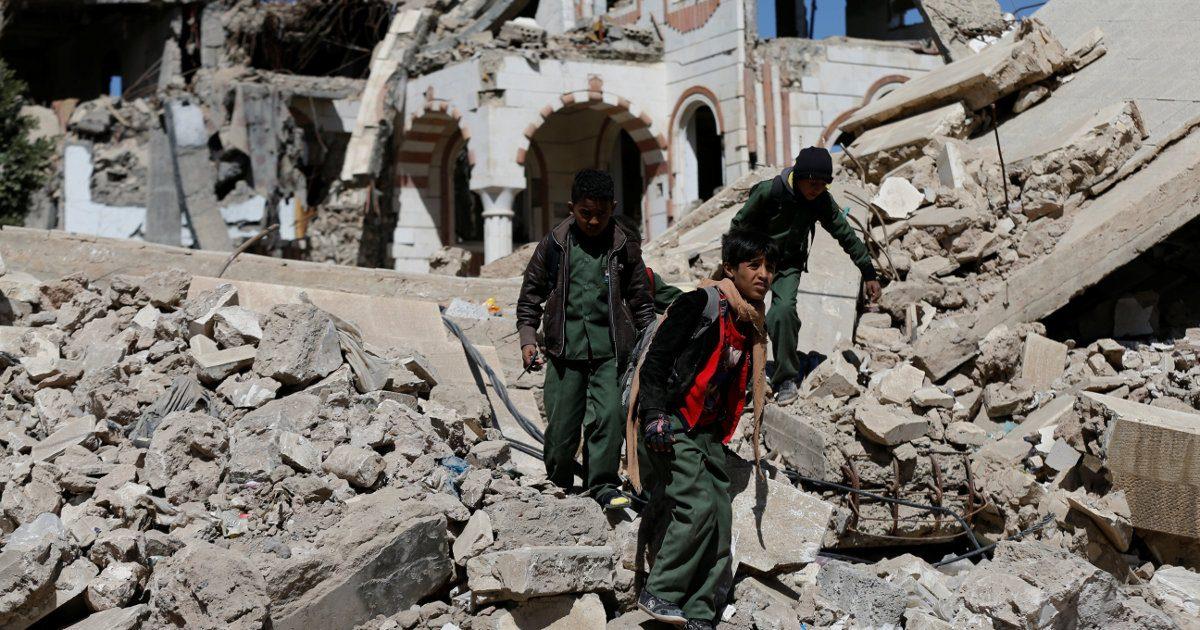 Unos niños caminan sobre unos escombros de edificios bombardeados en Yemen