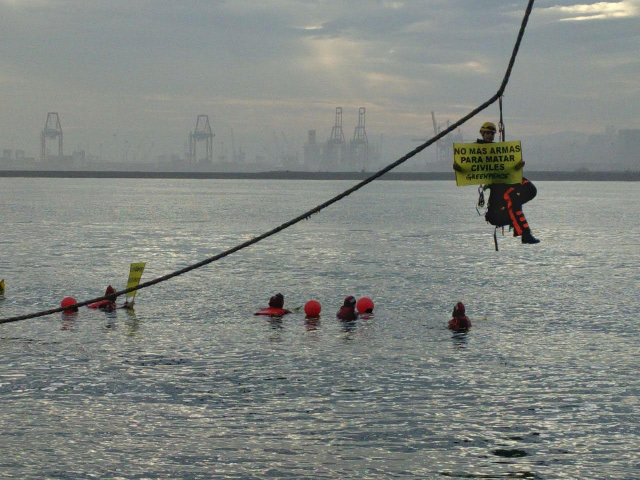 Un activistas colgado del amarre del buque en el puerto de Bilbao