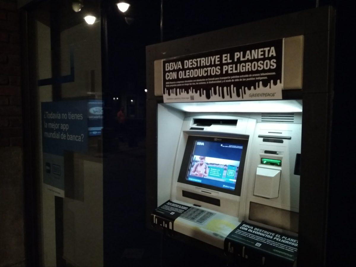 Cajero del BBVA en León con pegatinas que dicen BBVA destruye el planeta con oleoductos peligrosos