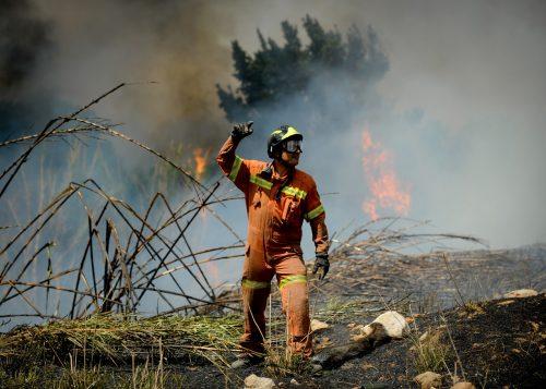 Un bombero da indicaciones mientras tratan de apagar las llamas del fuego en el incendio de Montserrat, en las proximidades de Valencia