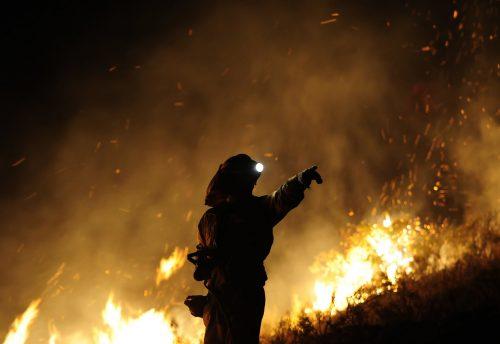 Un bombero da indicaciones mientras las llamas del fuego devoran un bosque tras él.