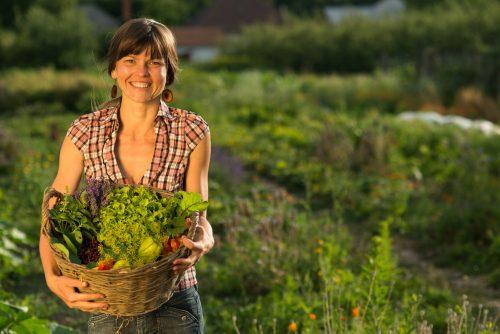 Una mujer sujeta una cesta con las frutas, vegetales y plantas medicinales que ella misma cultiva en Eslovaquia.